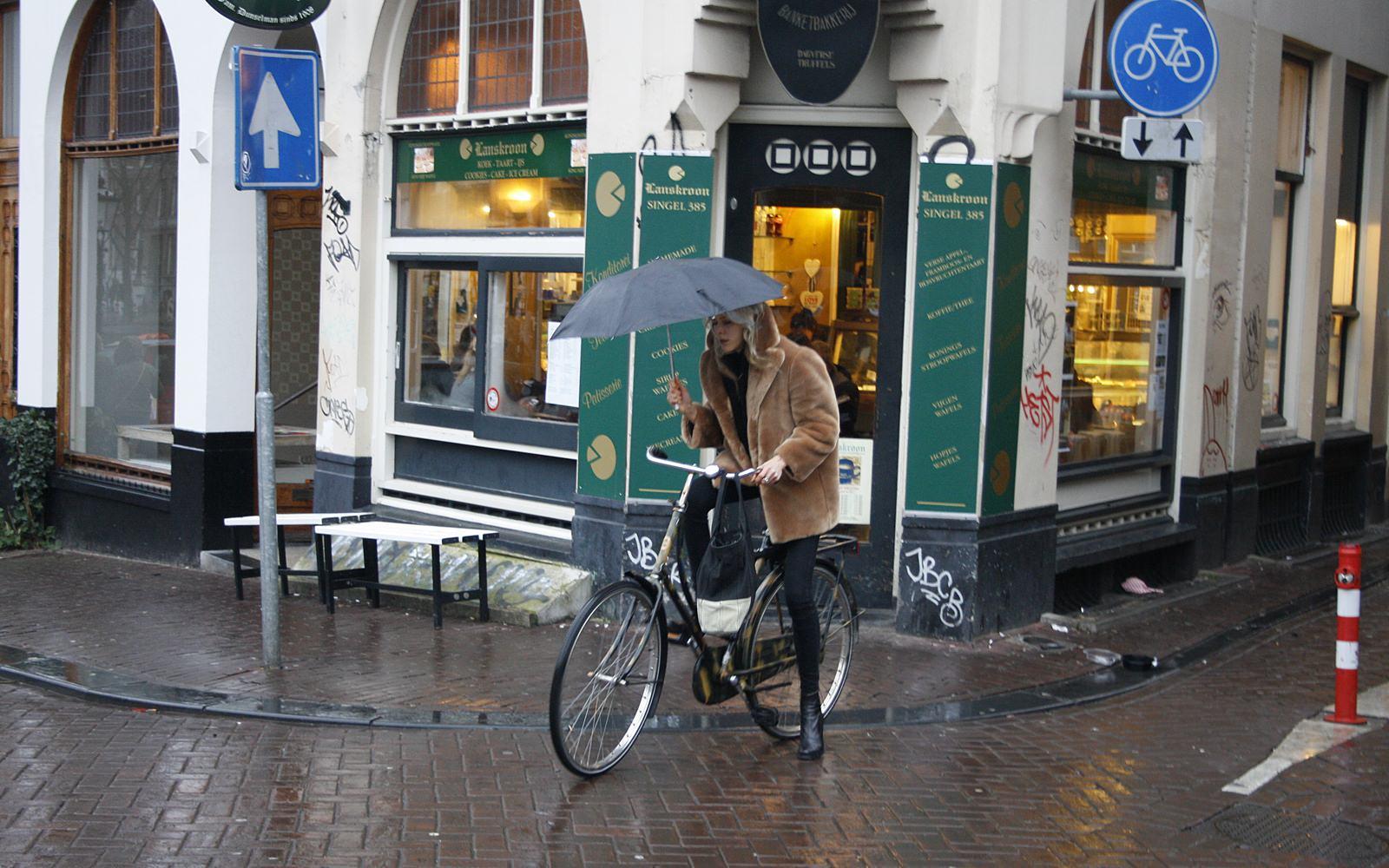 Mulher ciclista pedalando à chuva em Amesterdão