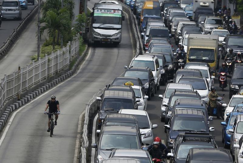 A man cycles past vehicles in a gridlocked street in Jakarta December 11, 2013.  REUTERS/Beawiharta